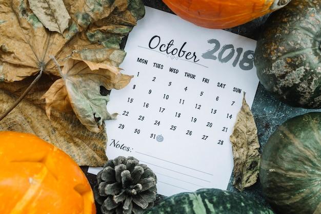 Calendario de octubre de 2018 que miente entre las calabazas y las hojas Foto gratis