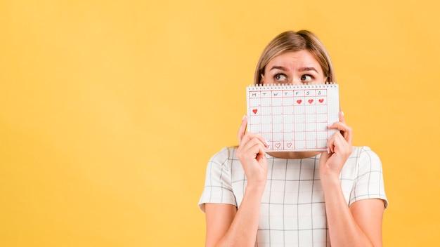 Calendario de períodos con formas de corazón dibujado y mujer cubriéndose la cara Foto gratis
