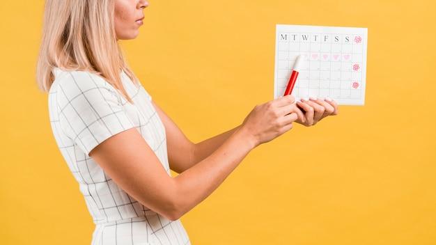 Calendario de períodos con formas de corazón dibujado y mujer de lado Foto gratis