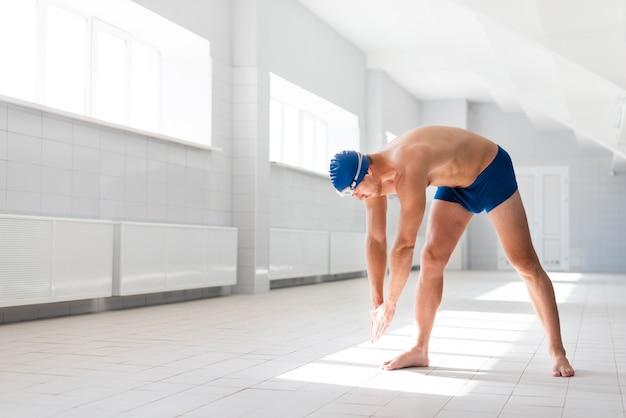 Calentamiento masculino antes de nadar Foto gratis