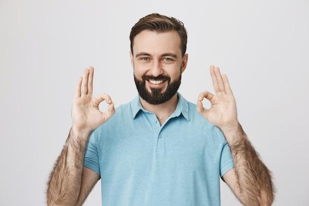 Calidad de garantía de cliente masculino complacido, muestra signo bien Foto gratis