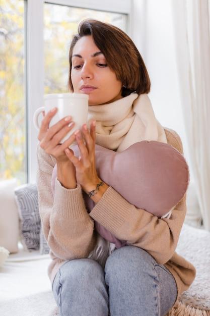 Cálido retrato de mujer sentada en el alféizar de la ventana con una taza de té caliente, café, vistiendo suéter y pañuelo blanco Foto gratis