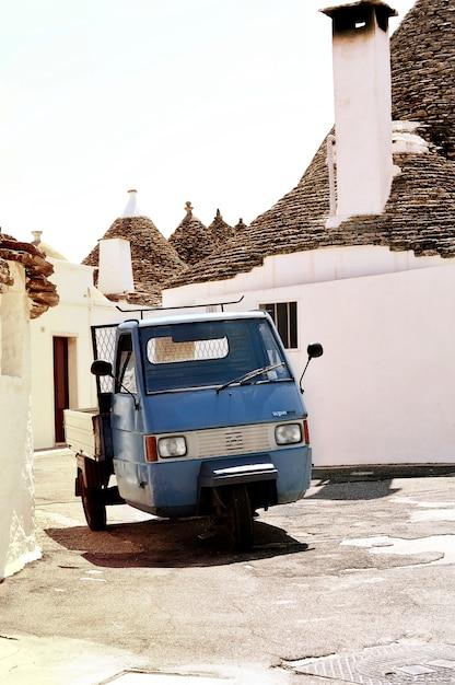 Calle con un coche pequeño azul Foto gratis