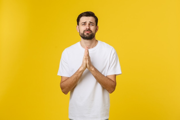 Calma y guapo. retrato de hombre joven guapo manteniendo las manos cruzadas y mirando pensativo. Foto Premium