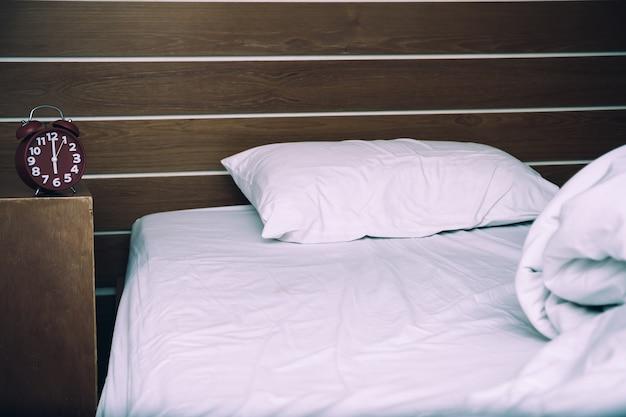 f2553c6073b8 Cama blanca desordenada y una almohada