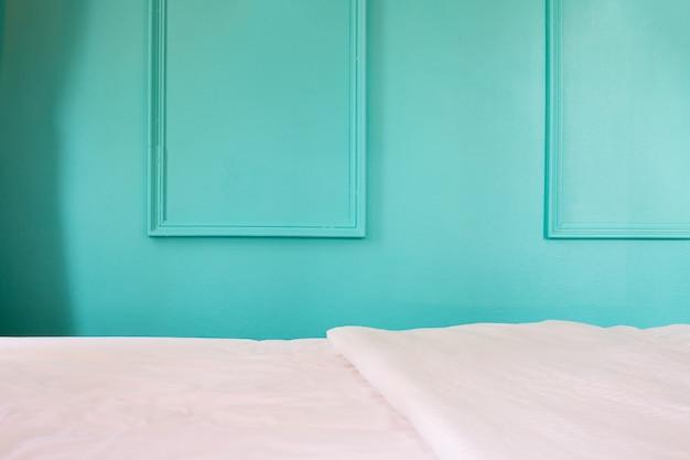 Cama blanca en fondo azul de la pared en dormitorio. Foto Premium