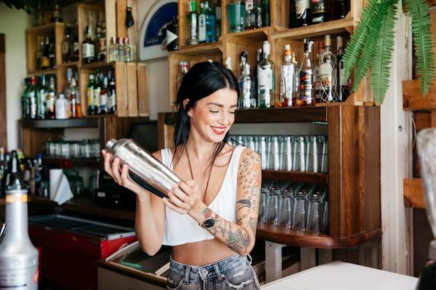 Camarera haciendo un cóctel Foto gratis