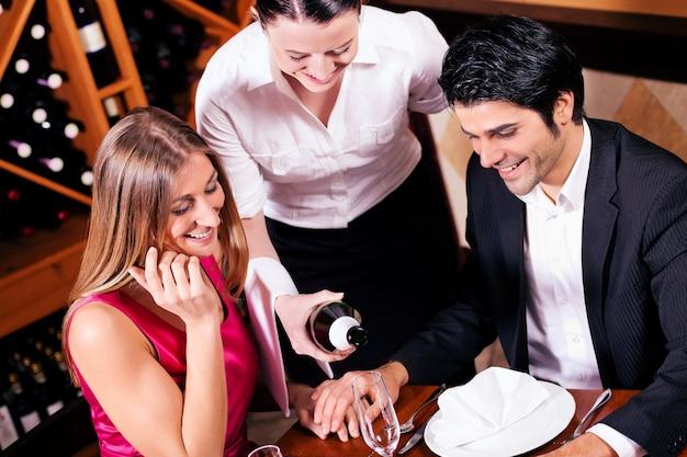 Camarera llenando vasos con champaña Foto Premium
