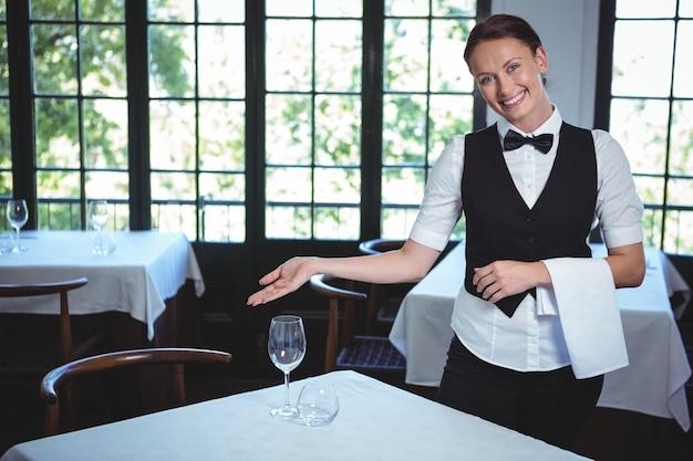 Camarera mostrando una mesa Foto Premium