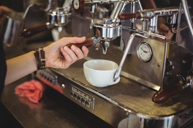 Camarera preparando una taza de café Foto gratis