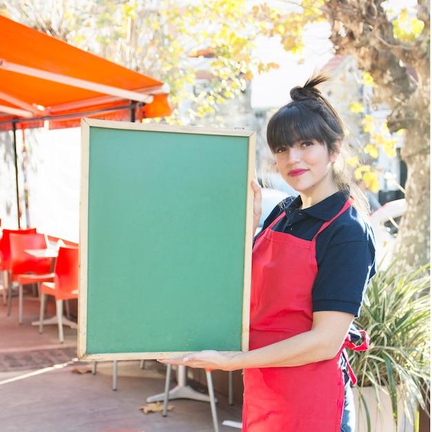 Camarera de sexo femenino que sostiene el tablero verde en blanco del menú en el café al aire libre Foto gratis