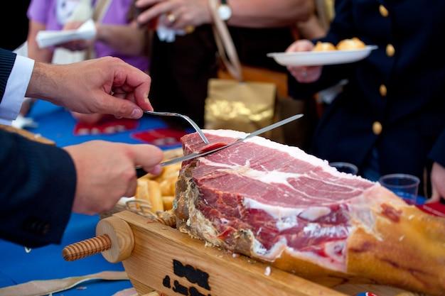 El camarero está cortando jamón Foto Premium