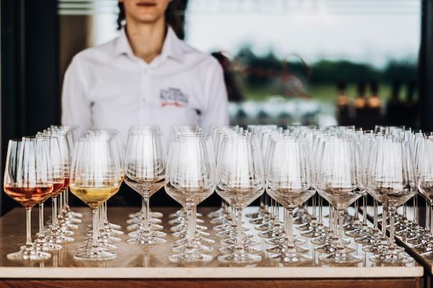 Un camarero se para detrás de muchos vasos Foto gratis