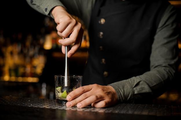 Camarero exprimiendo jugo de lima fresca con prensa de cítricos Foto Premium