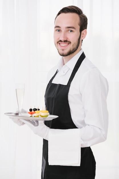 Camarero feliz con bandeja mirando a cámara Foto gratis