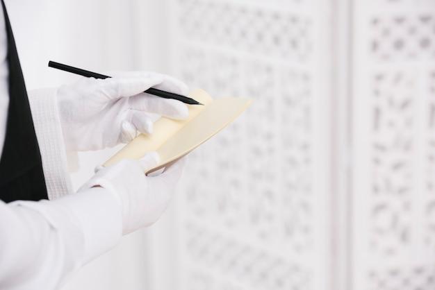 Camarero con guantes escribiendo orden en el bloc de notas Foto gratis