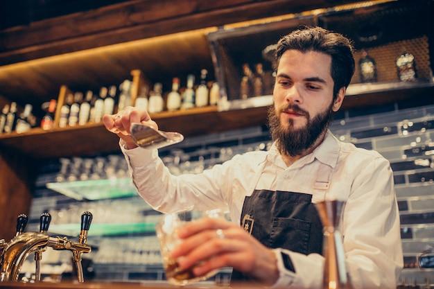 Camarero guapo haciendo beber y cócteles en un mostrador Foto gratis