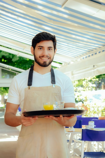 Camarero joven que sostiene la bandeja. Foto Premium