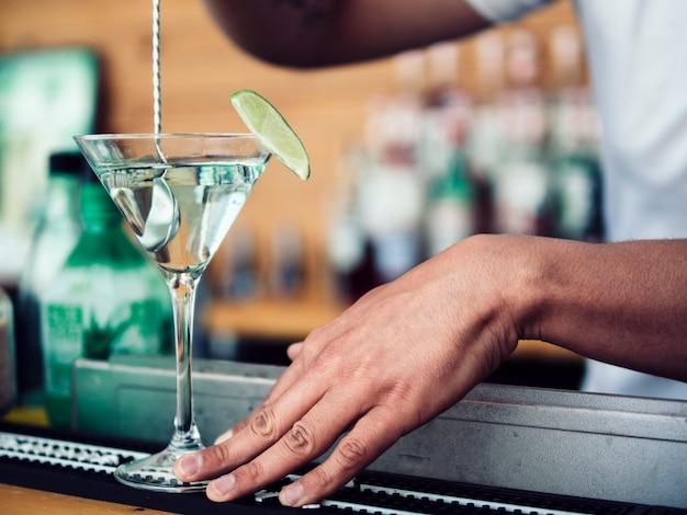 Camarero masculino revolviendo cóctel en copa de martini Foto gratis