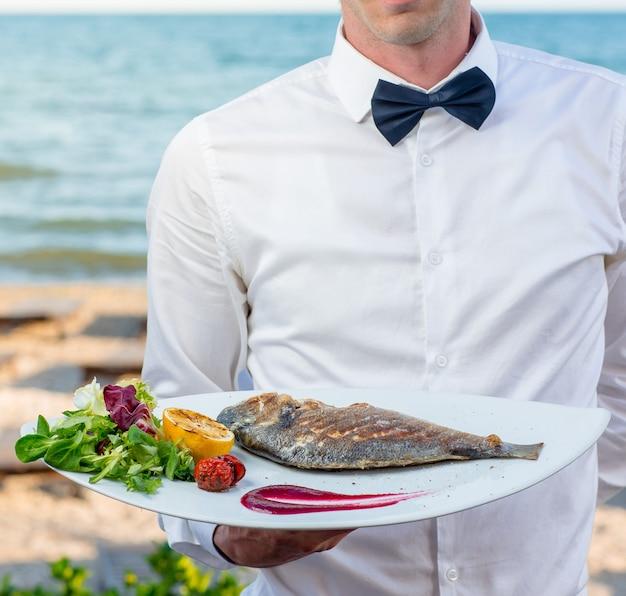 Camarero con plato de pescado a la parrilla con limón a la parrilla, tomate, espinacas frescas, lechuga Foto gratis