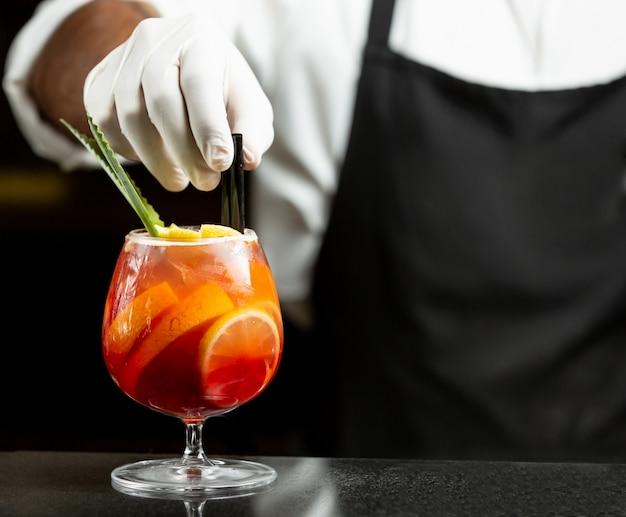 Camarero pone pajitas de plástico en cóctel de sangría en vaso Foto gratis