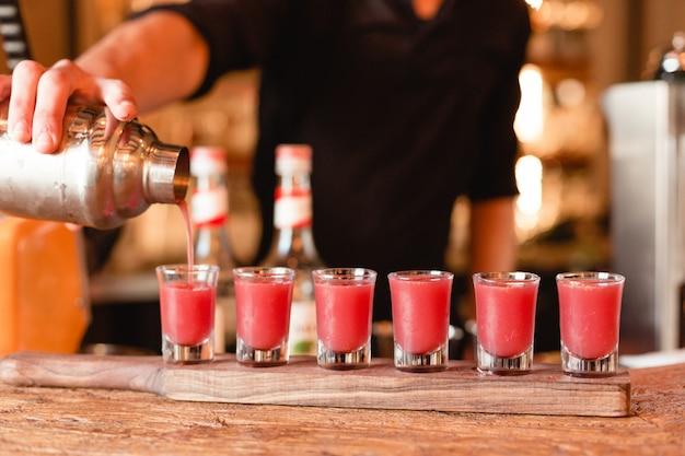 Camarero poniendo cócteles rojos en vasos pequeños de coctelera. Foto gratis