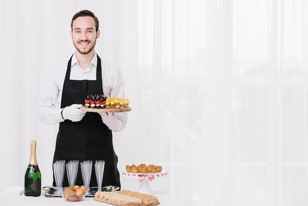 Camarero profesional presentando comida Foto gratis