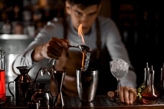 Camarero profesional que vierte una esencia de la cuchara en la llama al agitador de acero Foto Premium