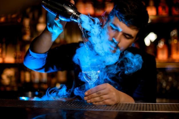 Camarero profesional que vierte un humo en la copa de cóctel desde la coctelera bajo la luz azul Foto Premium