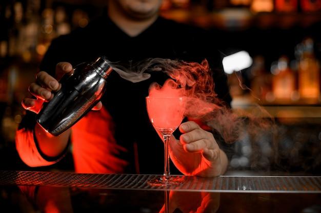 Camarero profesional que vierte un humo en la copa de cóctel desde la coctelera Foto Premium