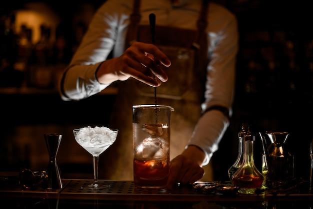 Camarero revolviendo un cóctel en la taza de vidrio de medición Foto Premium