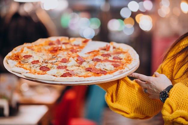 Camarero con sabrosa pizza de salami en un plato Foto gratis
