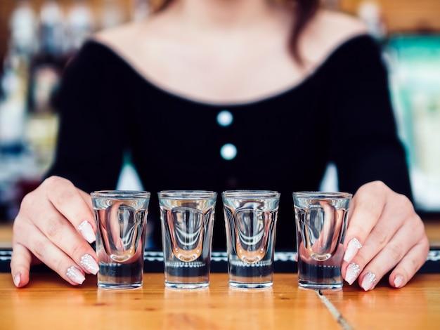 Camarero de sexo femenino con la fila de vasos de chupito Foto gratis