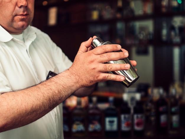 Camarero de sexo masculino que prepara la bebida en coctelera Foto gratis