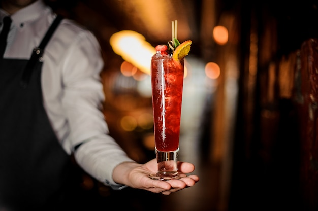 Camarero sosteniendo una copa de cóctel de zapateros frescos de verano decorado con fresa y menta Foto Premium