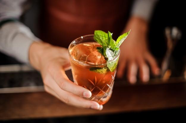 Camarero está sosteniendo un vaso de chupito con bebida alcohólica y menta Foto Premium