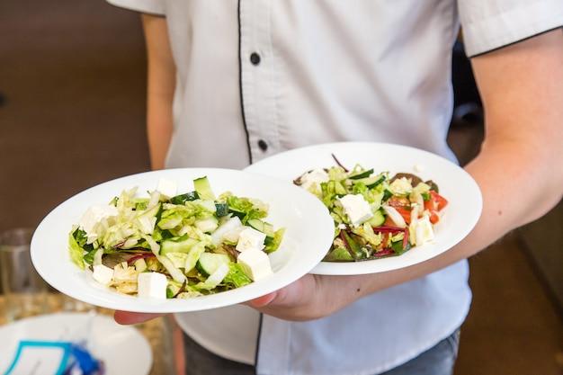Camarero sujetar dos platos de ensalada, trabajar en evento. Foto Premium