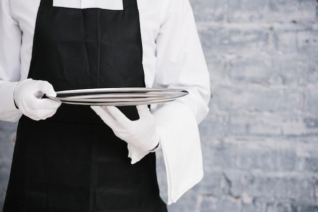 Camarero en uniforme con bandeja metálica Foto gratis