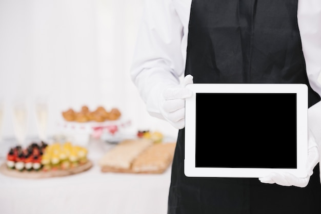 Camarero en uniforme sosteniendo una tableta con maqueta Foto gratis