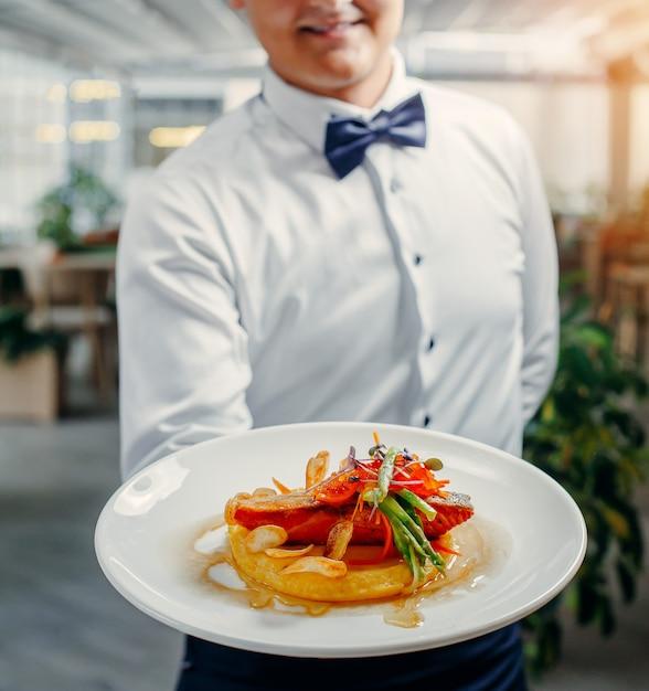 Camareros con plato de salmón a la parrilla, puré de papa, cubierto con caviar rojo, espárragos Foto gratis