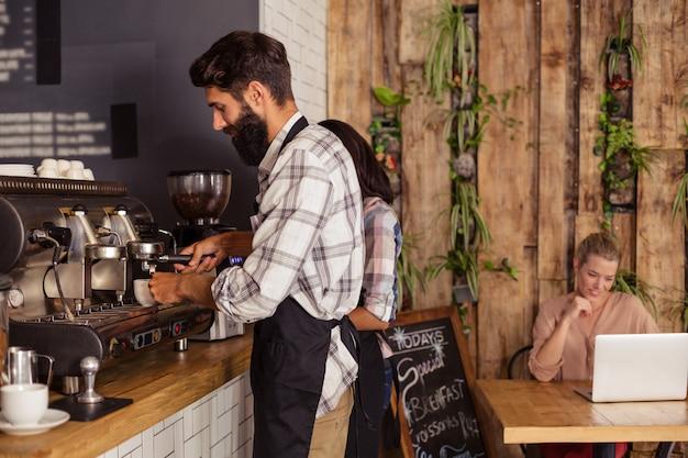 Los camareros que usan una máquina de café y el cliente en una computadora portátil Foto Premium