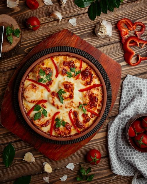 Camarones asados con queso, pimiento rojo en una sartén de cerámica Foto gratis