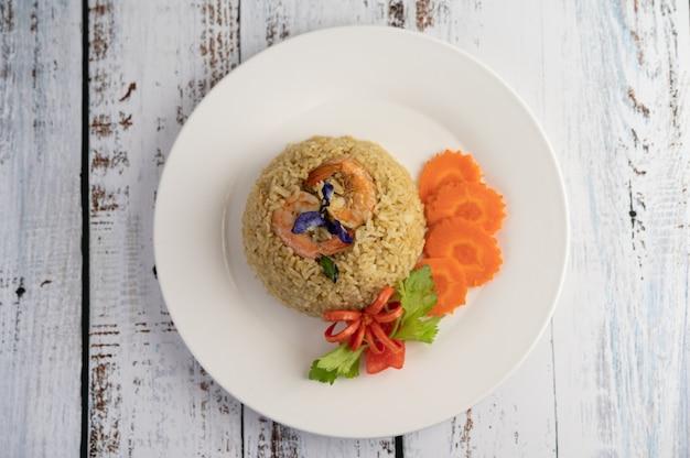 Camarones fritos de arroz en un plato blanco que consiste en tomates y zanahorias. Foto gratis