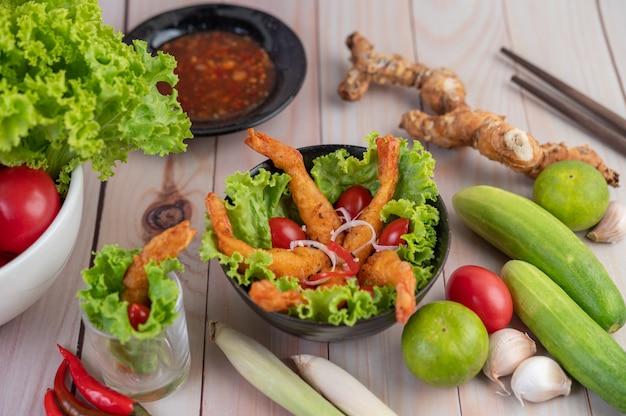 Camarones fritos rebozados en ensalada y tomates en un tazón de madera. Foto gratis