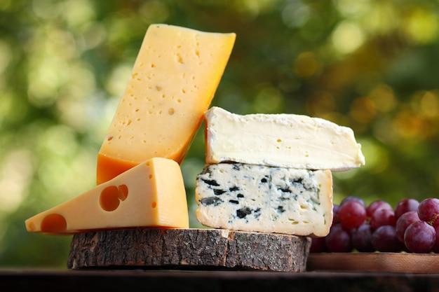 Camembert, queso brie, queso duro y queso azul sobre tabla de madera. rebanadas de varios quesos y uvas en borrosa Foto Premium