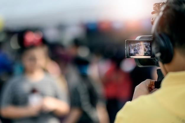 Cameraman grabando video de mujer joven, foco en pantalla de cámara. Foto Premium