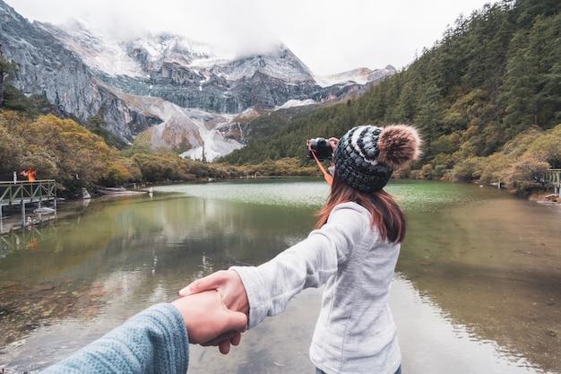 Caminando al viajero joven de la pareja que mira paisaje hermoso en la reserva natural de yading, concepto de la forma de vida del viaje Foto Premium