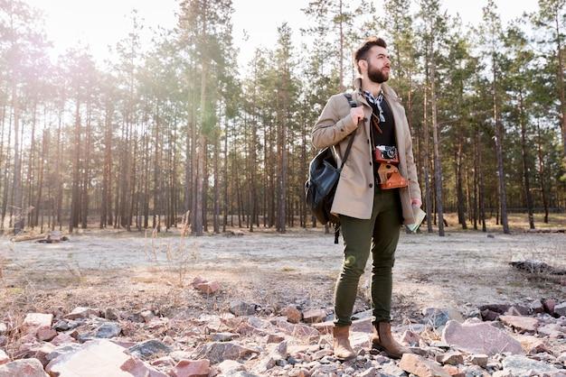 Un caminante masculino con cámara y mochila bolsa de pie en el bosque Foto gratis