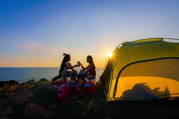 Caminantes que caminan con la mochila en una montaña en la puesta del sol. viajero va de campamento Foto Premium