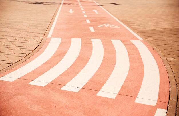 Caminata cruzada y signo de flecha direccional en carril bici con pavimento Foto gratis